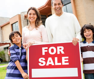 People posing with For Sale sign